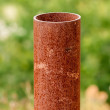 Vertical rusted metal pipe on green — Stock Photo #68193499