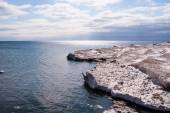 Dirty ice edge and melting floes by water under partly cloudy sk — Stock Photo
