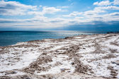 Dirty ice field near water under partly cloudy blue sky. — Stock Photo