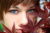 Portrait of Young Woman behind Red Leaves — Stock Photo