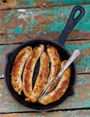Fried sausages on a frying pan — Stock Photo