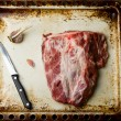 Piece of crude pork ready for roasting on a baking sheet. — Stock Photo #68556057