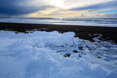 Black sand and white snow — Stock Photo