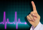 Doctor warning finger with heart rate monitor — Stock Photo
