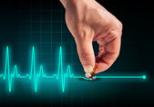 Hand putting out cigarette on heart beat line — Foto Stock