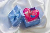 Blue present box with pink heart of glass in it — Stock Photo