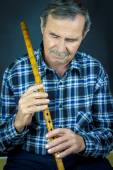 Man playing on pipe flute — Stok fotoğraf
