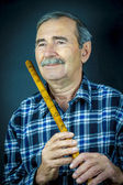 Man playing on pipe flute — Stock Photo