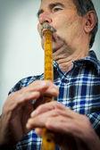Senior man playing on pipe flute — Zdjęcie stockowe