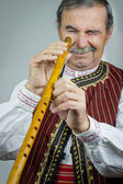 Pipe player in traditional clothing — Stock Photo