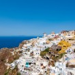 Colorful Oia village on the edge of the caldera cliffs with windmills in the distance on the island of Thira (Santorini), Greece. — Stock Photo #54796175