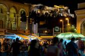 ATHENS-AUGUST 22: Nightlife on Monastiraki Square with Acropolis of Athens on the background on August 22, 2014 in Athens, Greece. — Stock Photo