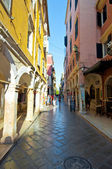 CORFU-AUGUST 27: Kerkyra narrow street in the old town with the row of souvenirs shops on August 27, 2014 on Corfu island, Greece. — Foto de Stock