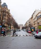 PARIS-JANUARY 10: Typically Parisian street and the Arc de Triomphe in the distance on January 10,2013. The Arc de Triomphe is situated at the western end of the Champs-Élysées in Paris, France. — Stock Photo