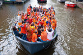 AMSTERDAM,NETHERLANDS-APRIL 27:  Crowd of people dressed in orange celebrate King's Day in a boat on April 27,2015 in Amsterdam. — Stock Photo