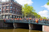 AMSTERDAM-APRIL 27:  Crowd of people watch the festival on the bridge during the King's Day (Koningsdag) on April 27, 2015. — Stock Photo