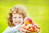 Happy girl holding a basket of apples. — Stock Photo