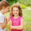 The little boy whispers a secret on an ear to the girl. — Stock Photo #51947043