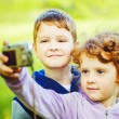 Happy little boy and girl taking self photo in the autumn park. — Stock Photo #52676257