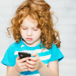 Little girl playing on a smartphone on a light background. — Stock Photo #53064621