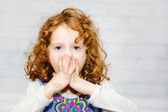 Little girl covering her mouth with her hands. Surprised or scar — Stock Photo
