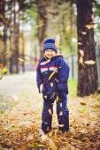Niño feliz lanza las hojas de otoño en el aire. — Foto de Stock