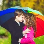 Little girl and boy hiding under an rainbow umbrella from the ra — Stock Photo #55935887