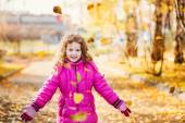 Little girl in a red jacket, throwing autumn leaves in the air.  — Stock Photo