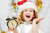 Happy little girl in Santa hat holding a clock in his hands. Chr — Stock Photo