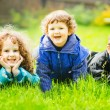 Happy children lying on grass and smiling. — Stock Photo #56541029