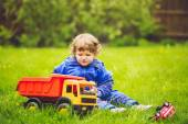 A child plays a toy car on the grass in the park. — Stock Photo
