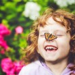 Laughing girl with a butterfly on his nose. — Stock Photo #56737507