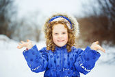 Happy little girl sends a kiss, playing in the snow park. — Stock Photo