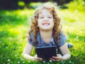 Little girl sitting on grass and playing tablet pc, instagram fi — Stock Photo