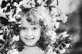 Black and white portrait of a little girl with spring flowers in — Stock Photo
