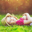 Curly girl lays on the grass in summer park. Background toning f — Stock Photo #76459165