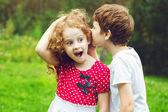 Маленький мальчик и девочка шепотом. — Стоковое фото
