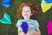 Laughing girl with paper airplane in her hand on green lawn. — Stock Photo