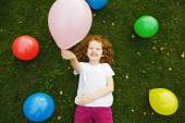 Happy little girl holding colored balloon, lies on green grass a — Stock Photo