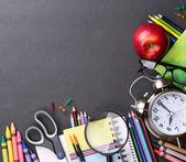 Books, apple, alarm clock and pencils on black board background. — Stock Photo