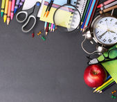 Books, apple, alarm clock and pencils on black board background. — Stock Photo