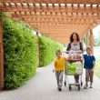 Happy family walking with shopping cart — Stock Photo #56622163