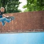 Skateboarder jumping in halfpipe at skatepark. — Stock Photo #56628145