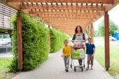 Happy family walking with shopping cart — Stock Photo
