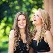 Two beautiful girls laughing together outdoors — Stock Photo #56637563