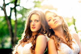 Two beautiful girls outdoors backlight portrait.  — Stock Photo