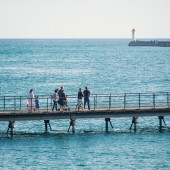 People walking on footbridge over the water. — Stock Photo