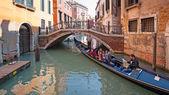Tourists enjoying a tour on gondola in Venice. — Stock Photo