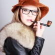Lady wearing a hat and holding a smoking pipe — Stock Photo #65582191