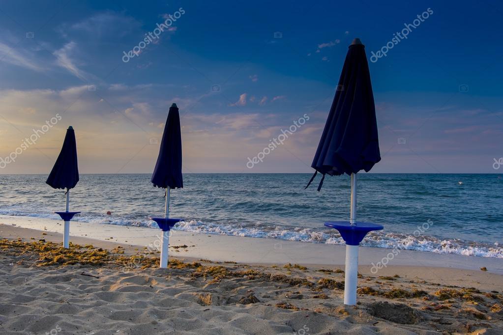 Spiaggia abbandonata con ombrelloni chiusi foto stock for 3 piani di design da spiaggia
